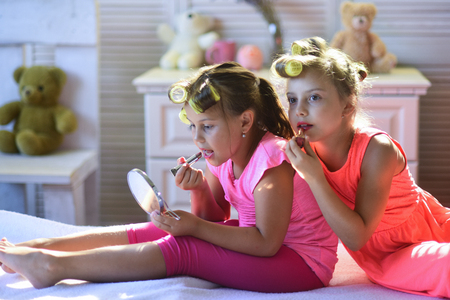 Little girls do makeup sitting in room with toys. Girls with calm faces and curlers play with accessories in childroom. Children sit on bed with lipstick and mirror. Beauty and kids fashion concept.
