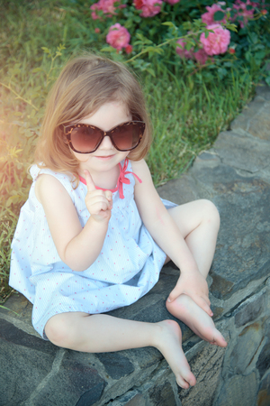 Baby girl smiling in sunglasses with raised finger on stone border with bare feet. Child and childhood. Summer vacation concept.
