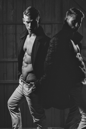 Two young men with sexy body showing their muscular torso and abs in open shirts