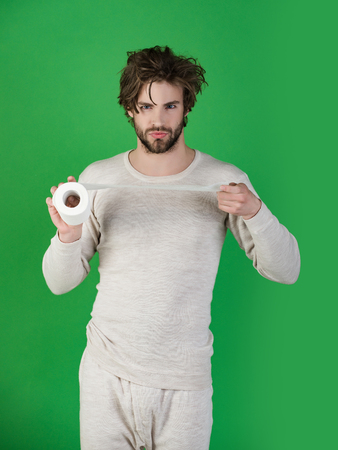 Man with serious face hold toilet paper, single. Hygiene and sanitary. WC and restroom. Sterility and purity. Man in underwear with disheveled hair, morning. diarrhea