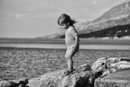 Cute baby boy child with curly blond hair in green shirt plays at rocky sea beach on summer day Banque d'images - 94518378