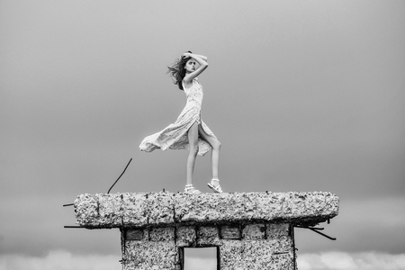 Pretty cute sexy blonde woman or girl stands with raised hand in blue dress waving on wind outdoor on broken concrete bunker Фото со стока