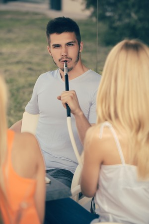 Man vapor hookah pipe with girls in shisha bar lounge. Celebration, party concept. Addiction, bad habits. Date, love triangle, relations. Stock Photo