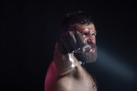 Fist with blood of bearded man on black background. Hipster with beard, mustache shout with anger. Power, might, magic. Sport, boxing, fighting. Halloween, holidays celebration, copy space