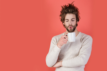 Cold and flu, single. Man with disheveled hair drink mulled wine. Sleepy guy with tea cup on red background. Insomnia, refreshment and energy. Morning with coffee or milk, copy space Stock fotó