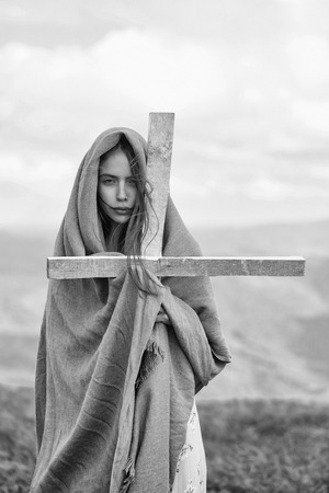 Pretty sexy young cute girl or woman with serious face wrapped in veil holding cross on meadow Stock fotó
