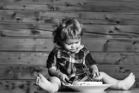 Cute baby boy child with blond curly hair eats delicious cake with blueberries sitting on wooden table