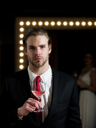 meeting. man or businessman with beard and hairstyle in formal outfit with red tie hold wine glass near woman in mirror, relax, bar and restaurant, sommelier, tasting and degustation Banco de Imagens