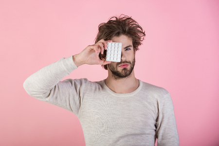 Health and medicine, hangover. Dieting pill and vitamin, man with anabolic. Cold, flu and headache treatment, hypnotic tablet. Man with pills in blister pack. Drug and antidepressant, insomnia. Stock Photo