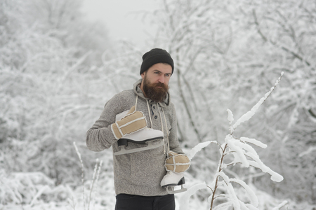 Bearded man with skates in snowy forest. Temperature, freezing, cold snap, snowfall. Winter sport and rest, Christmas. skincare and beard care in winter. Man in thermal jacket, beard warm in winter.