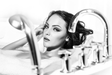 One attractive passionate young brunette sexy naked woman with wet long curly hair lying in bath tab with chrome cock water and foam on white backdrop, horizontal picture