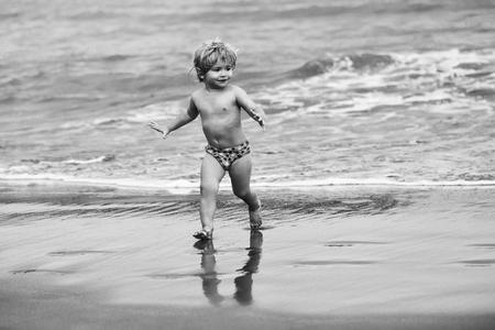 トランクでブロンドの髪のポニーテールを持つかわいい陽気な男の子は、自然の背景に波と海や海の水に沿って湿った砂浜で実行されます 写真素材
