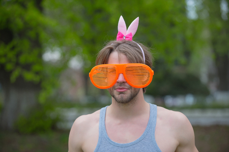 man, playboy, valentines day, easter., love games. sexy muscular man in glasses and pink ears on natural background. fashion and party celebration. spring and summer season. Stock Photo