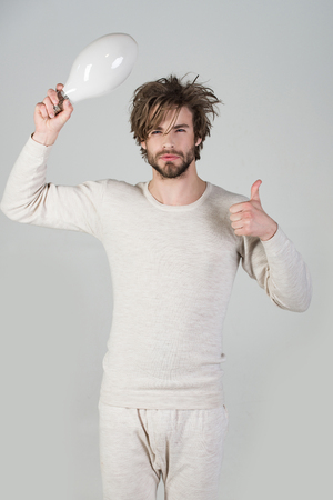 Man with disheveled hair hold big lamp, thumb up. Energy and electricity concept. Solution and decision. Power and business success. shouting guy has an idea on grey background, morning.