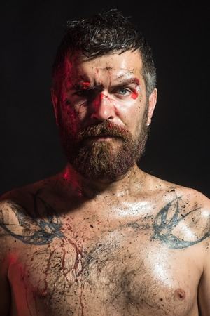 Magic, enchantment, witchcraft. Bearded hipster with tattoo on chest on black background. Man with beard, mustache on brutal bloody face. Wizard, sorcerer, warlock. Halloween, holidays celebration