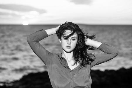 風の強いブルネットの髪を持つかわいい女の子やセクシーな女性は、自然の背景に日没時に青い海のビーチでポーズ 写真素材