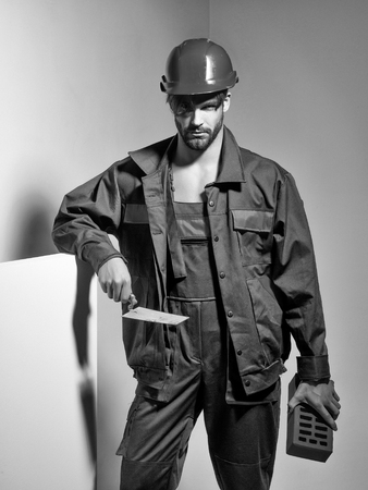 Handsome man builder construction mason worker bricklayer in orange hard hat and boilersuit keeps brick and trowel on grey background Reklamní fotografie