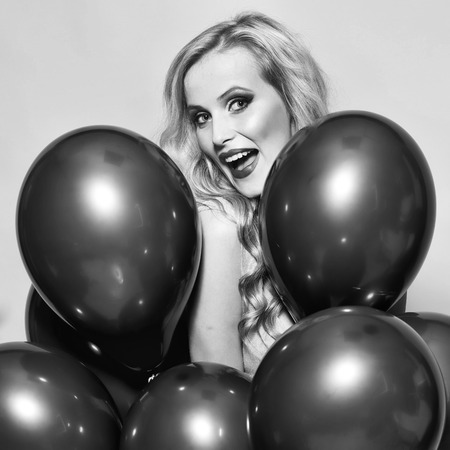 One beautiful smiling flirtatious young happy blond woman with long curly hair standing in bunch of red party balloons in studio on yellow backdrop, square picture Stock Photo