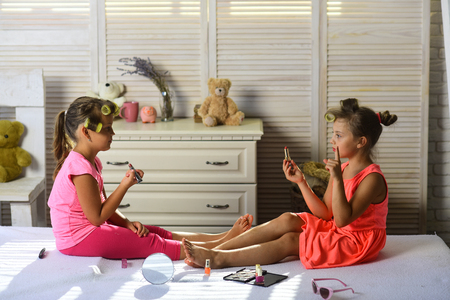 Little girls do makeup sitting in room with toys. Beauty and fashion concept. Girls with curlers and serious faces play with accessories. Children sit on bed with lipstick, nail polish and mirror.