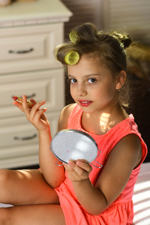 Kid with makeup accessories in childroom. Beauty and kids makeup concept. Little girl with curlers and cheerful face wears fashionable dress indoors. Child sits on bed with pink lipstick and mirror.