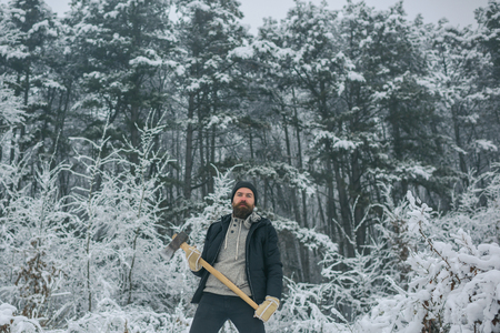 Temperature, freezing, cold snap, snowfall. Man lumberjack with ax. Bearded man with axe in snowy forest. Camping, traveling and winter rest. skincare and beard care in winter, beard warm in winter.