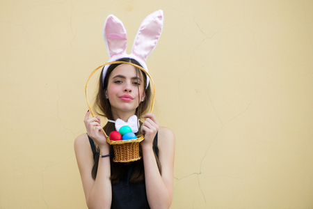 Easter woman with rosy bunny ears on beige background. Girl holding wicker basket with colored eggs. Fertility and rebirth concept. Easter tradition and symbol. Spring holiday celebration, copy space 版權商用圖片