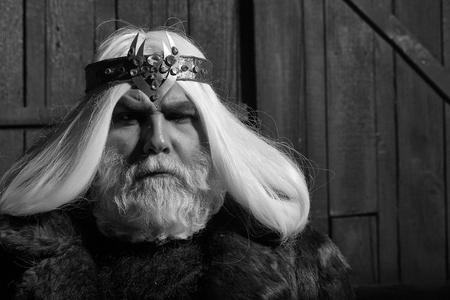 毛皮のコートと宝石の宝石ジュエリーで王冠に深刻な顔と髪に長いひげを持つ古いドルイドひげの男 写真素材