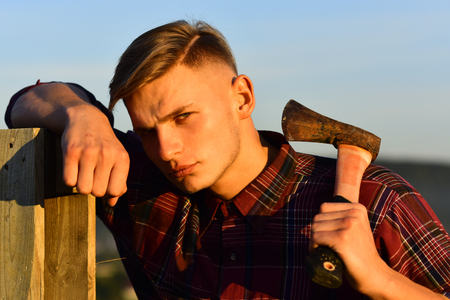 man with axe at wooden fence on sunset sky