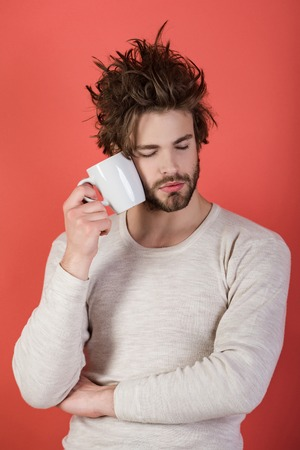 Morning with coffee or milk. Insomnia, refreshment and energy. Man with disheveled hair drink mulled wine. Sleepy guy with tea cup on red background. Cold and flu, single. Stock fotó