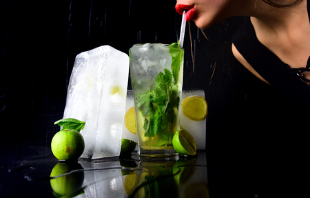 Bar and restaurant, lemonade. woman drink mojito with lime and mint. Thirst and refresh. Party and summer vacation. Cocktail with ice cube for young girl isolated on black.