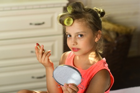 Little girl with curlers and cheerful face wears dress indoors. Beauty and kids makeup concept. Child sits on bed with pink lipstick and mirror. Kid with moms makeup accessories in childroom.