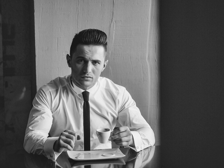 Man young handsome elegant model wears white shirt black skinny necktie sits at table holds cup of coffee and looks in camera indoor on grey background Фото со стока