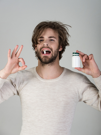Drug and antidepressant, insomnia. Health and medicine, hangover. Man with pills in jar. Cold, flu and headache treatment, hypnotic tablet. Dieting pill and vitamin, man with anabolic.