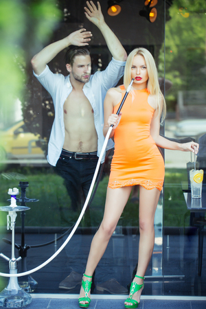 Woman sensual with hookah pipe in bar. Couple man with girl at shisha cafe lounge. Date, love, relationship. Celebration, party concept.