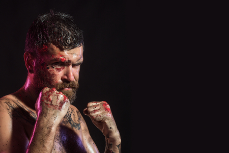 Man in fight position with blood paint on face, fists. Bearded hipster with tattoo on chest skin on black background. Power, might, magic. Sport, boxing, fighting. Halloween, holidays, copy space
