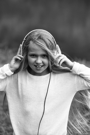 small girl kid with long blonde hair and pretty smiling happy face in white with headphones on head standing outdoor near water on green natural background