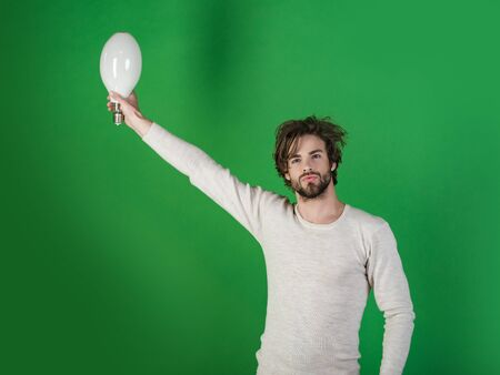 Man with disheveled hair hold big lamp. guy has an idea on green background, morning. Power and business success. Energy and electricity concept. Solution and decision. Banque d'images - 95003037
