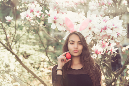 easter egg in hand of woman or adorable girl with sexy, plush lips and rosy bunny ears on long, brunette hair at blossoming, magnolia flowers, trees, garden on floral background. Easter. Spring 版權商用圖片