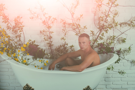 sexy man in bathtub at spring blossom, spa. Spring relax in bathroom. Beauty and spa, health, wellness. Spa and hygiene, macho man with muscular body sit in bath, body care.