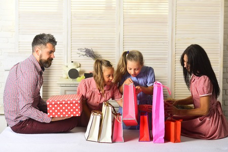 Family with cheerful faces open presents at home. Mother, father and daughters with shopping bags and packs. Happy family and shoping concept. Man, woman and adorable children with gifts at home.