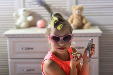 Little girl with curlers and lipstick in room with toys. Girl paints lips with serious face sitting on bed in childroom. Child wears sunglasses and takes cosmetics. Makeup and kids fashion concept.