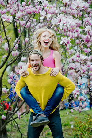 Spring, nature and environment. Couple in love in blossoming flower, spring. Love and romance, relationship, happy couple. Sensual woman and man in magnolia bloom. Man and woman in spring, easter. Stock Photo