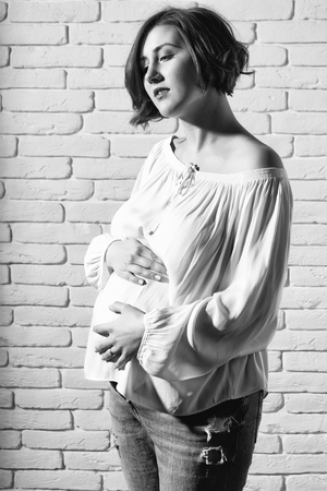 pretty happy sexy woman or cute pregnant girl with round belly or abdomen in white blouse on brick wall background at mothers day holiday Stock Photo