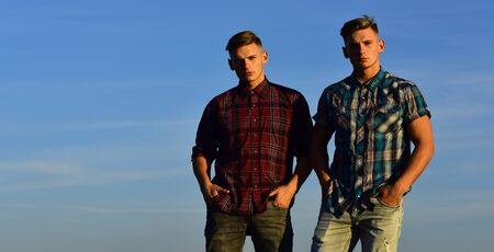 Man twins with athletic body, family values. man brothers posing on blue sky background, copy space