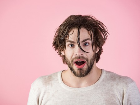 Morning washing, wake up, everyday life. Man splash water at face on pink background. Hygiene, guy wash surprised face. Refreshment and healthcare. Man with disheveled wet hair washing face. Stock fotó