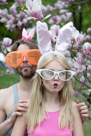 couple in love making fish lips, face grimace in glasses and rosy, bunny ears. Pretty girl or cute woman and handsome man or macho on blossoming, floral environment. Spring. Easter, celebration