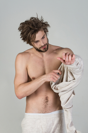 Insomnia, energy, single with uncombed hair. Barber and hairdresser, male fashion. Sleepy man with beard on grey background. Man with disheveled hair in underwear. Morning wake up, everyday life. Stock Photo