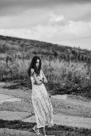 Pretty girl slim female model with long brunette hair in blue dress on summer field on natural background