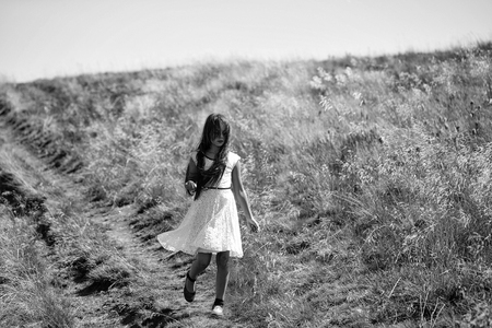 Small beautiful walking brunette pensive girl in white lace summer dress in hill valley with deep dry grass sunny windy day outdoor on natural background with blue sky, horizontal picture
