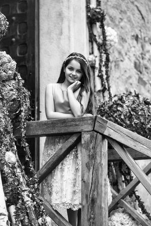 長いブルネットの髪と花の装飾屋外の近くの木製の階段に立って笑顔のドレスと花輪のかわいい女の子